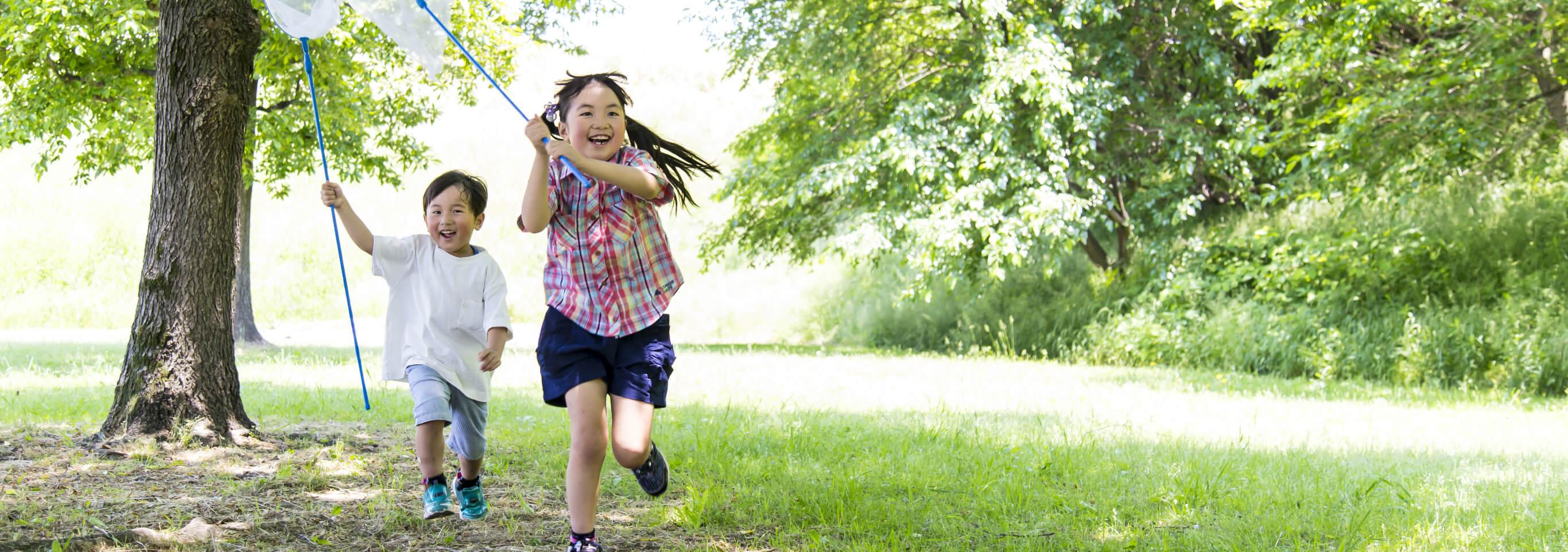 緑の多い公園で子供2人が遊んでいる画像